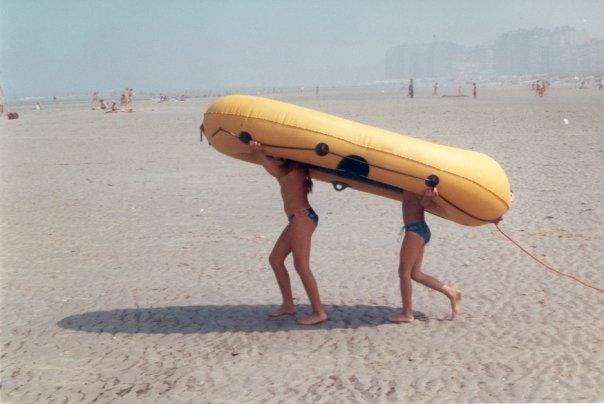 kinderen onderen rubberen bootje op het strand, op weg naar de zee