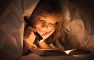 Reisboekenclub-meisje-leest-boek-met-zaklamp-onder-de-lakens