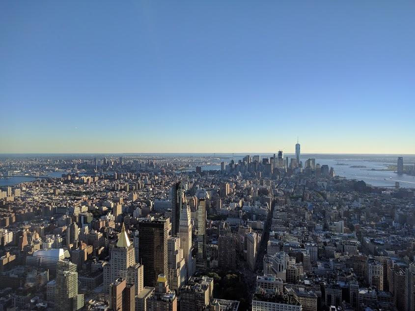 Zicht op One en Vrijheidsbeeld vanuit Empire State Building