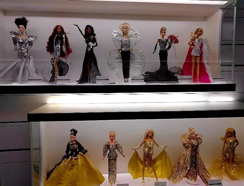 Barbie's in goudkleurige kledij en zwart/wit/zilver kledij op een rij