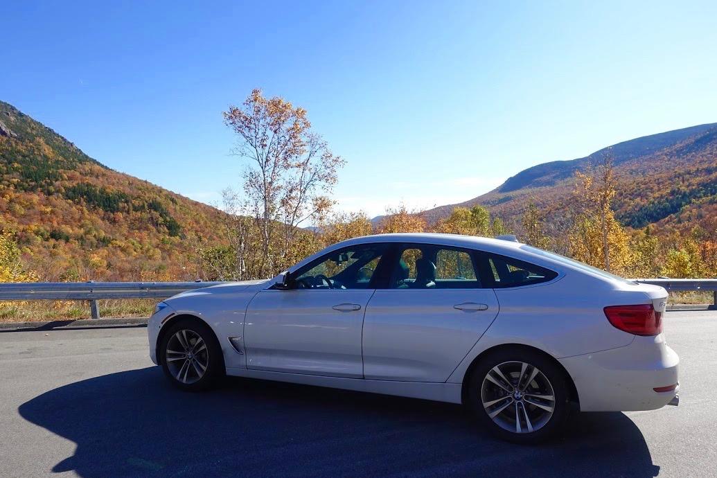 Witte BMW auto met op de achtergrond de indrukwekkende White Mountains in NH, tijdens de herfstrit
