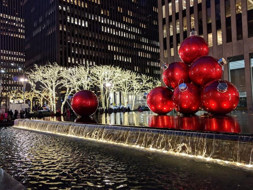 Kerstornamenten op 6th Avenue, Kerst in NYC - rode kerstbollen op water