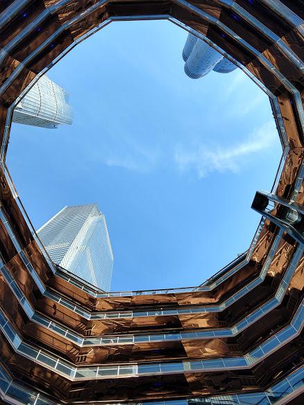 Vanbinnen, in het centrum van The Vessel, zicht op een blauwe hemel en de wolkenkrabbers van de Hudson Yards