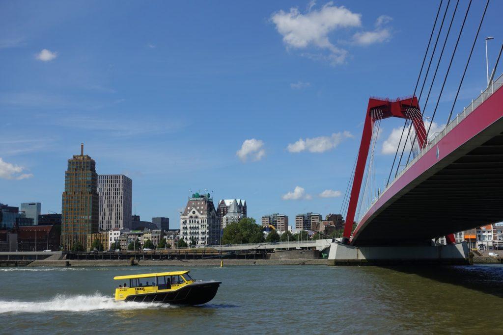 Rode Willemsbrug, gele watertaxi op de Nieuwe Maas en Witte Huis in de Stadsdriehoek in de verte, Rotterdam