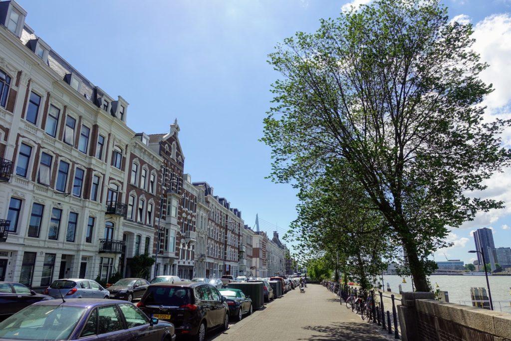 Noordereiland in Rotterdam, oude woningen aan de Maaskade, zicht op water en in de verte de Erasmusbrug