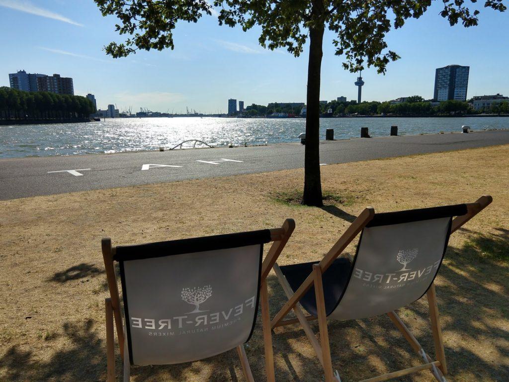 Strandstoelen op de Wilhelminapier met zicht op de Nieuwe Maas en Euromast in Rotterdam
