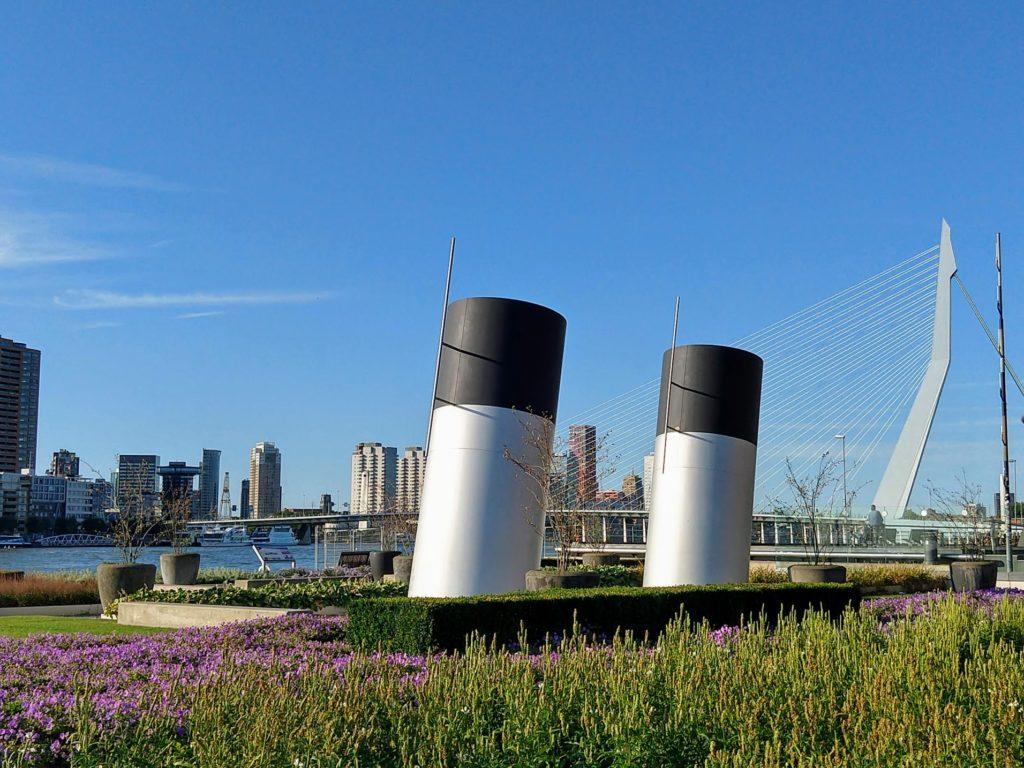Kunstwerk schoorstenen van grote schepen verwerkt in de tuin op Wilheminapier met zicht op de Nieuwe Maas en de Erasmusbrug in Rotterdam